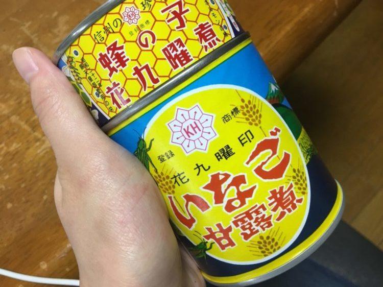 蜂の子といなごの缶詰が縦に重なっている