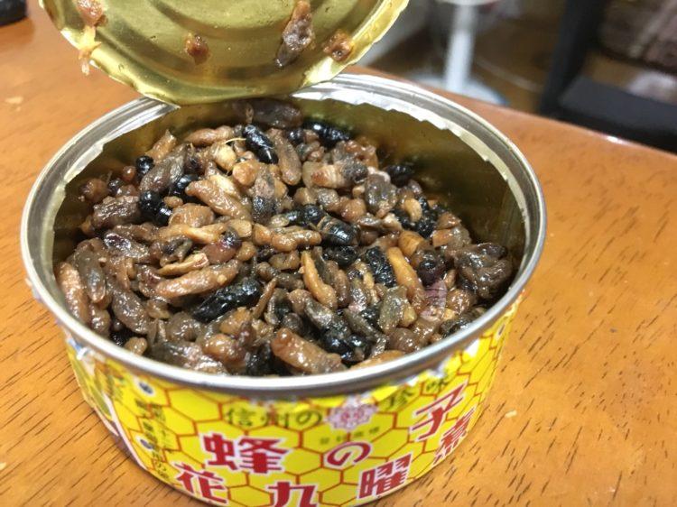 蜂の子の缶詰が開封され、上から中身が見えている